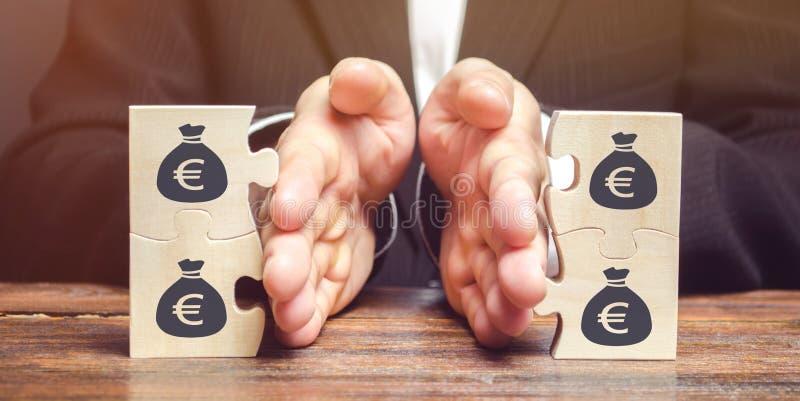 O homem de negócios separa o enigma de madeira com uma imagem do dinheiro O conceito da gestão financeira e da distribuição dos f imagens de stock