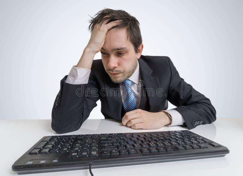 O homem de negócios sobrecarregado e esgotado está trabalhando com computador fotos de stock