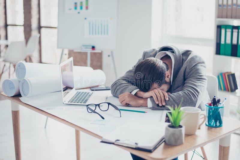 O homem de negócios sobrecarregado novo cansado está dormindo na tabela em m fotos de stock royalty free