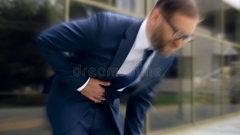 O homem de negócios sofre da dor de estômago afiada, gastrite, azia, efeito tonto imagem de stock royalty free