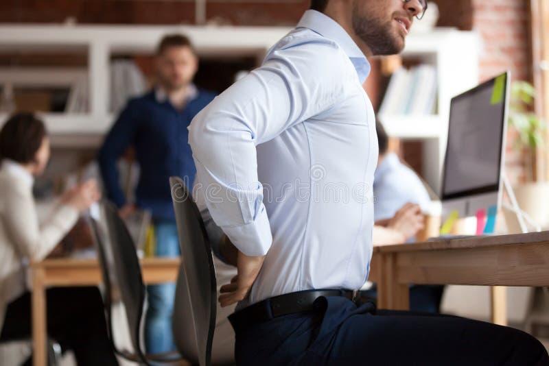 O homem de negócios sofre de uma mais baixa dor nas costas que senta-se no escritório compartilhado imagens de stock royalty free