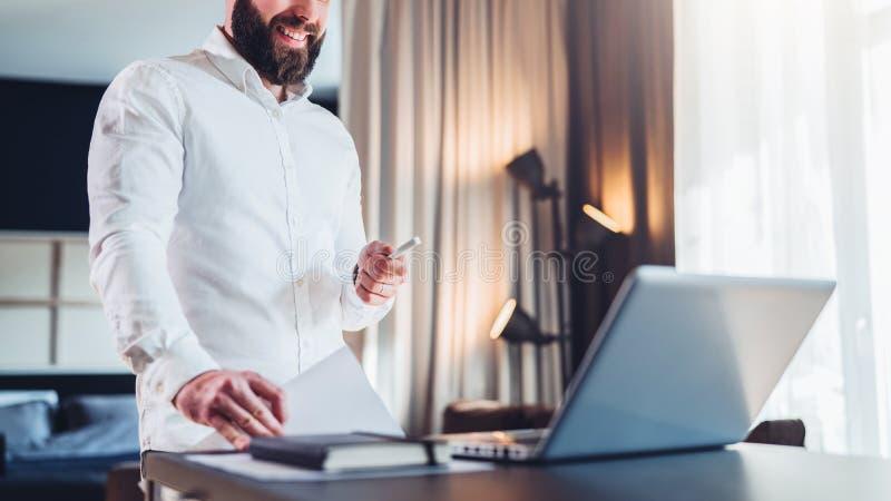 O homem de negócios de sorriso farpado novo na camisa branca é mesa próxima ereta na frente do portátil, terra arrendada em seus  imagens de stock royalty free