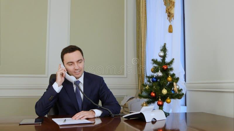 O homem de negócios de sorriso que pegara o telefone e felicita colegas do negócio com Natal fotografia de stock