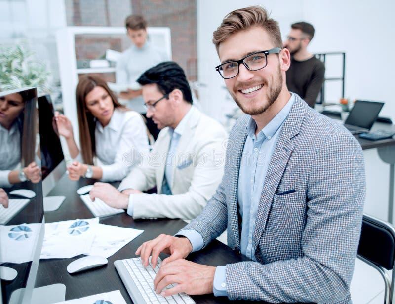 O homem de negócios de sorriso usa um computador para analisar dados financeiros fotos de stock royalty free