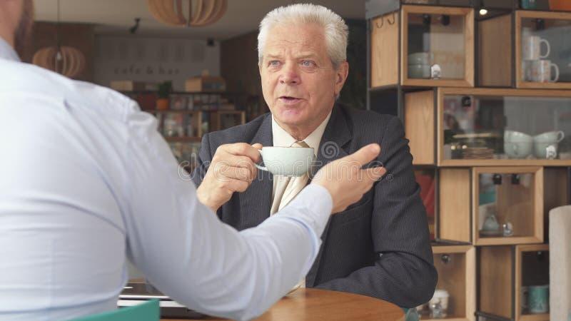 O homem de negócios superior escuta seu sócio imagem de stock
