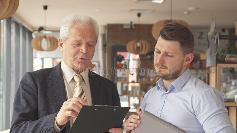 O homem de negócios superior explica algo na prancheta a seu sócio fotografia de stock