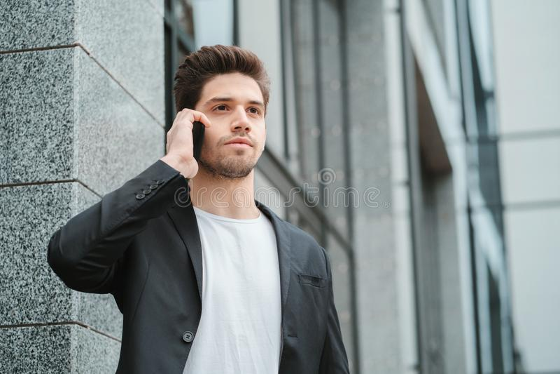 O homem de negócios tem a conversação séria usando o telefone celular Indivíduo do negócio em negociações formais do terno atenta fotos de stock royalty free