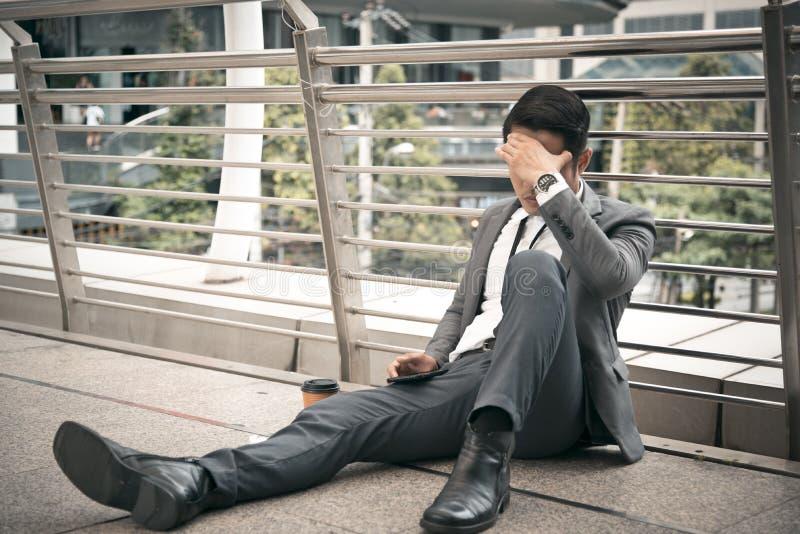 O homem de negócios tem a dor de cabeça e o conceito forçado, desempregado, conceito falido, conceito insalubre fotografia de stock