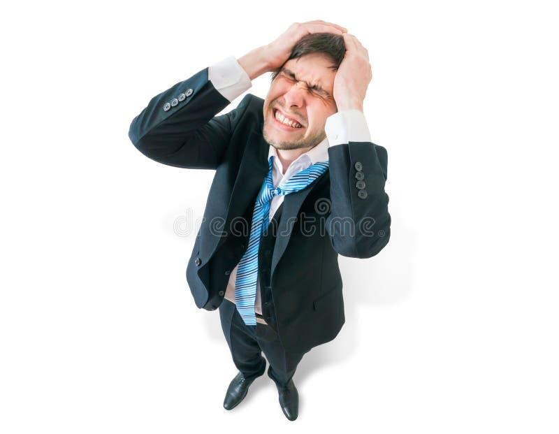 O homem de negócios tem a dor de cabeça e está guardando sua cabeça Vista da parte superior imagens de stock