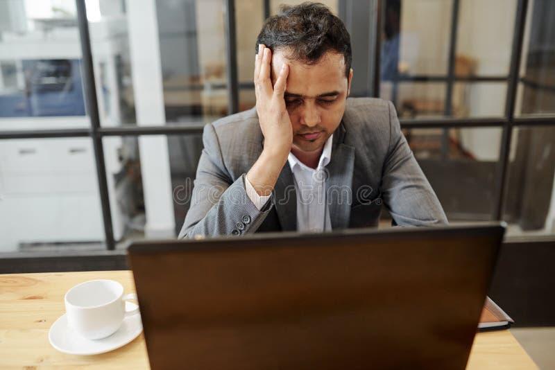 O homem de negócios tem uma dor de cabeça durante o dia do trabalho foto de stock