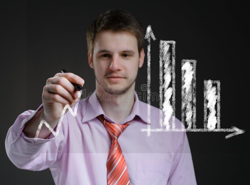 O homem de negócios tira em gráficos transparentes de uma tela. imagens de stock royalty free