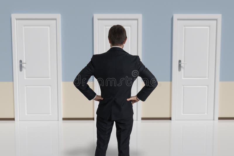 O homem de negócios de trás está fazendo a decisão e está selecionando a porta foto de stock royalty free
