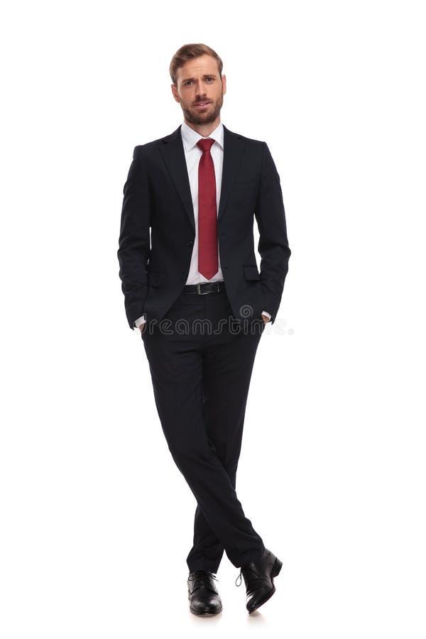 O homem de negócios triste está com mãos em uns bolsos no fundo branco foto de stock