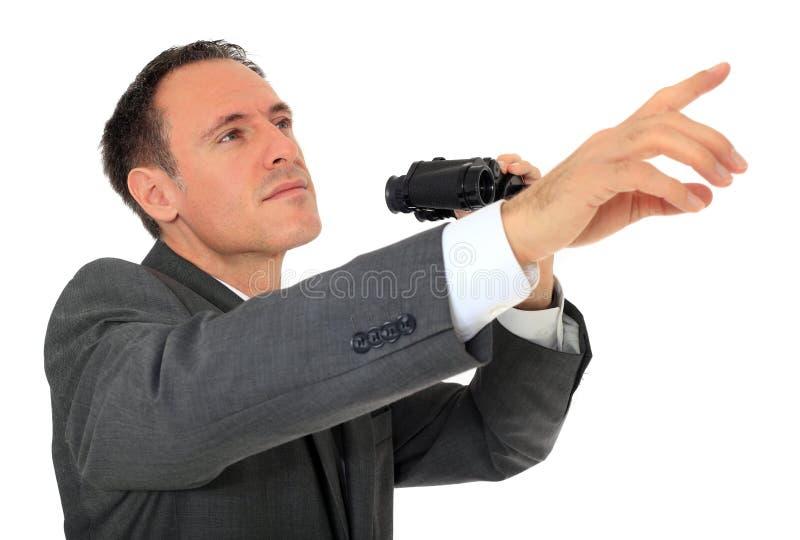 O homem de negócios usa o spyglass e os pontos com dedo fotos de stock