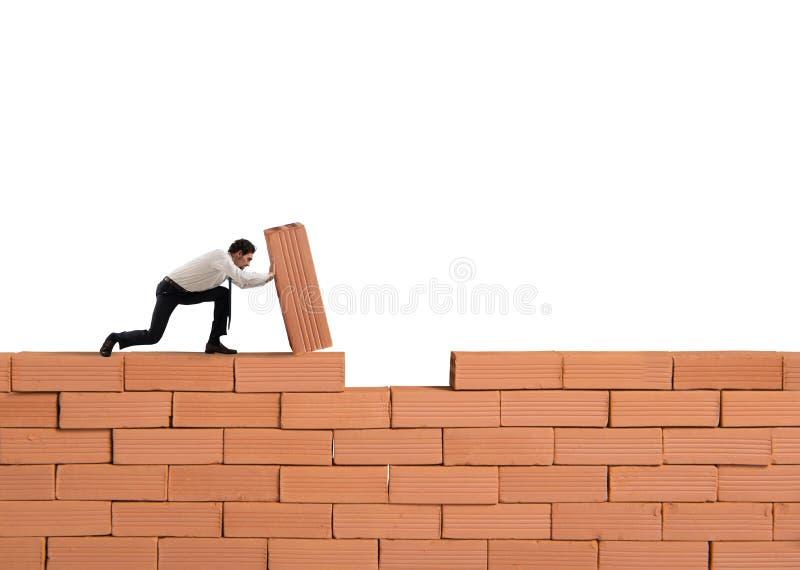 O homem de neg?cios p?e um tijolo para construir uma parede Conceito do neg?cio, da parceria, da integra??o e da partida novos foto de stock royalty free