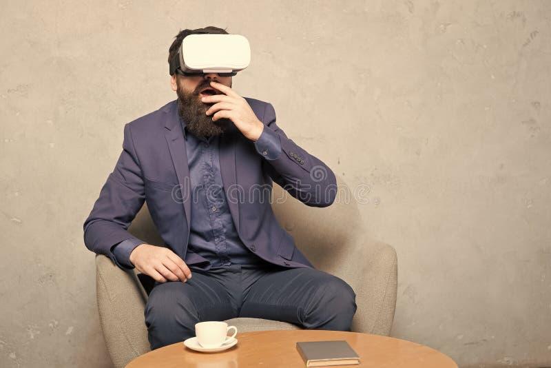 O homem de neg?cios senta a cadeira veste o hmd para explorar a realidade virtual ou a AR S?cio comercial interativo na realidade imagem de stock royalty free