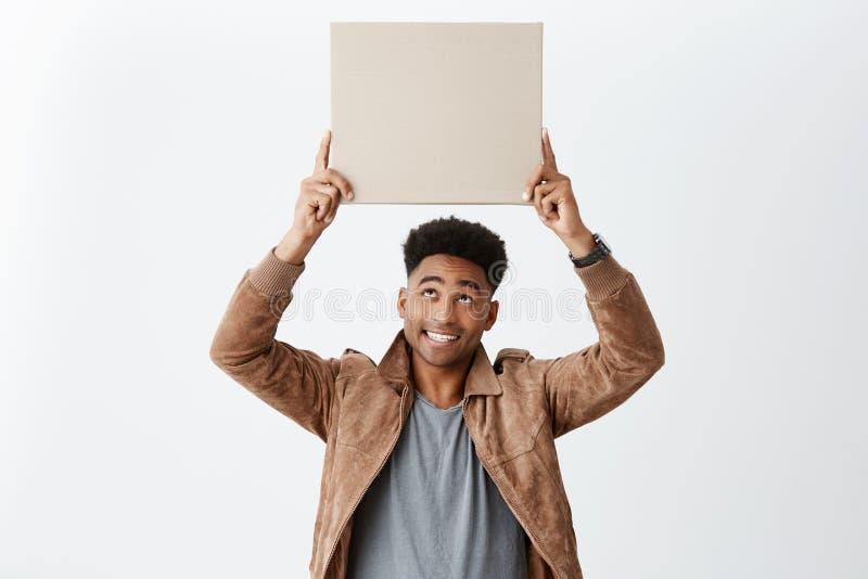 O homem de pele escura alegre novo feliz com penteado afro no moderno à moda veste guardar o cartão bisbilhota, olhando fotos de stock