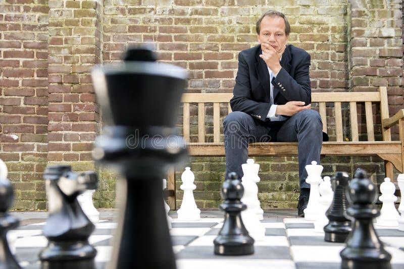 O homem de pensamento que senta-se em uma vida fez sob medida a placa de xadrez exterior imagem de stock