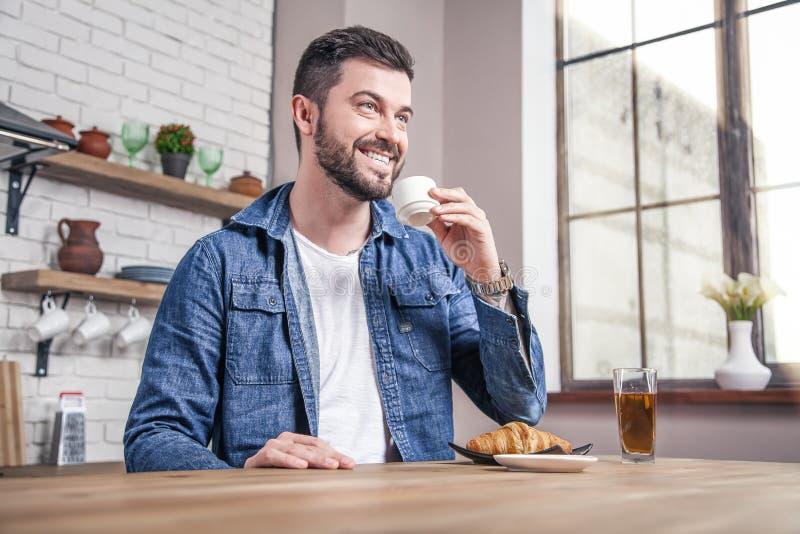 O homem de sorriso considerável novo está bebendo seu café da manhã com croissant e um suco de maçã na cozinha fotografia de stock
