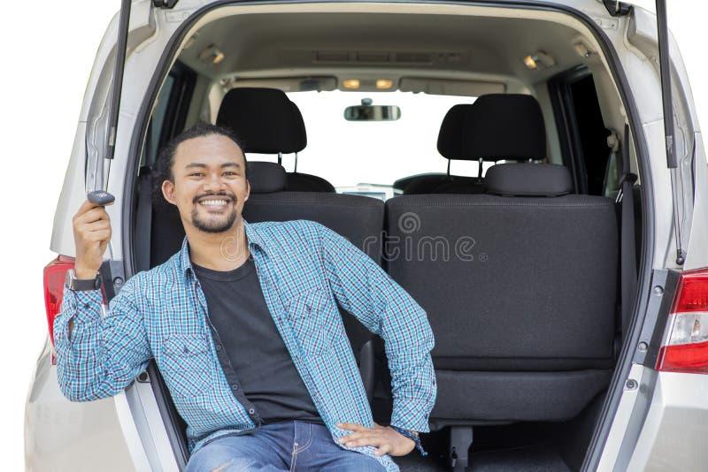 O homem de sorriso do Afro guarda uma chave nova do carro no tronco de carro fotografia de stock