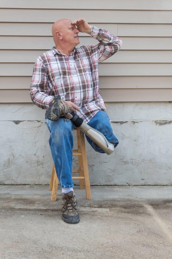 O homem de sorriso do amputado que senta-se em um tamborete, pé protético cruzou-se, protegendo eyes a vista acima foto de stock royalty free