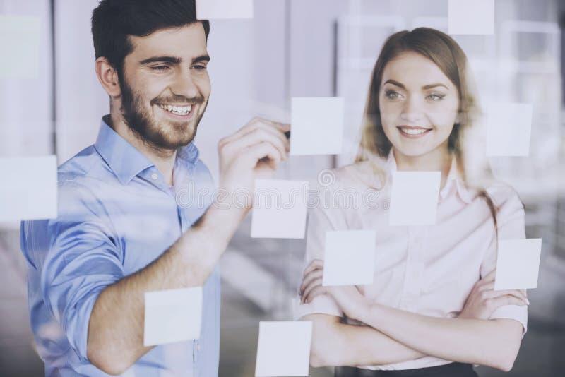 O homem de sorriso escreve ideias em etiquetas no vidro fotos de stock royalty free