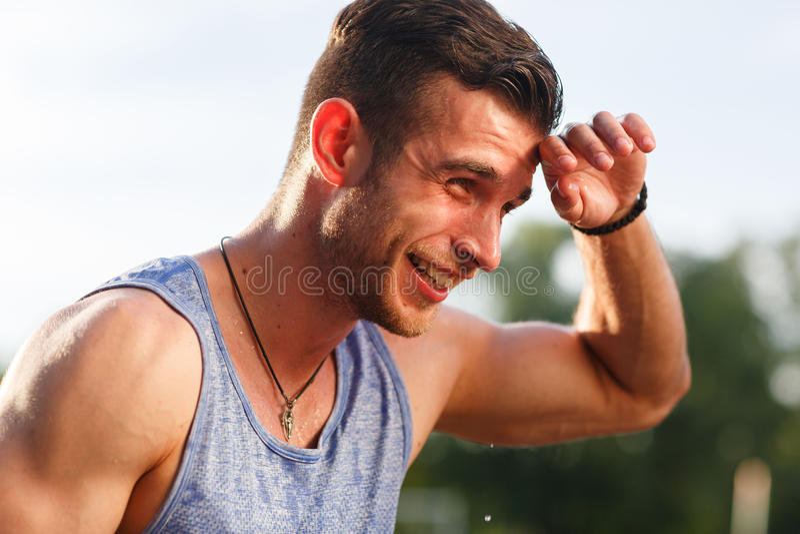 O homem de sorriso na limpeza azul do t-shirt suou na natureza foto de stock royalty free