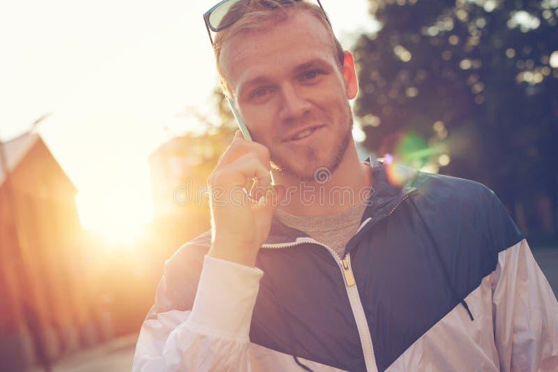 O homem de sorriso novo com telefone celular tem uma conversação, por do sol na rua fotografia de stock royalty free