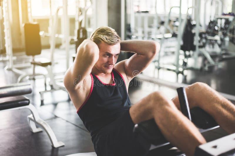 O homem de Storng que fazem o situp ou as triturações no gym, homens exercitam o estômago muscular fotografia de stock