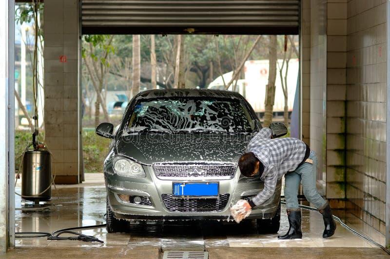 O homem de Yaan China-Um está limpando o carro imagens de stock