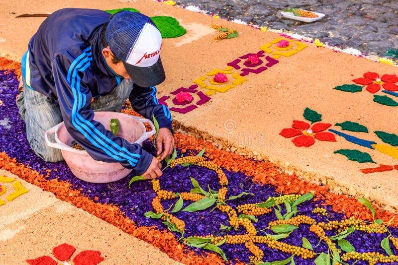 O homem decora o tapete emprestado serragem tingido, Antígua, Guatemala fotos de stock royalty free