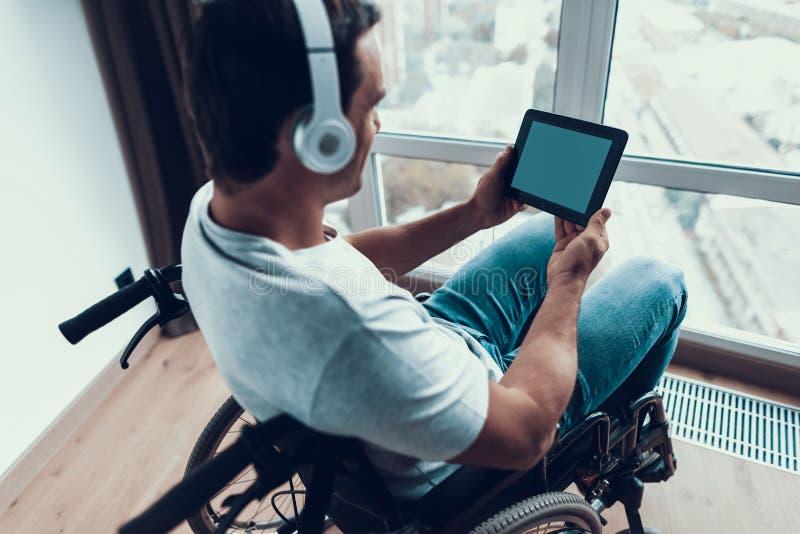 O homem deficiente da vista traseira nos fones de ouvido usa a tabuleta foto de stock royalty free