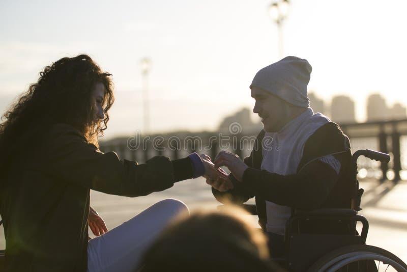 O homem deficiente dos jovens na cadeira de rodas faz uma proposta a sua amiga na luz solar fotografia de stock royalty free