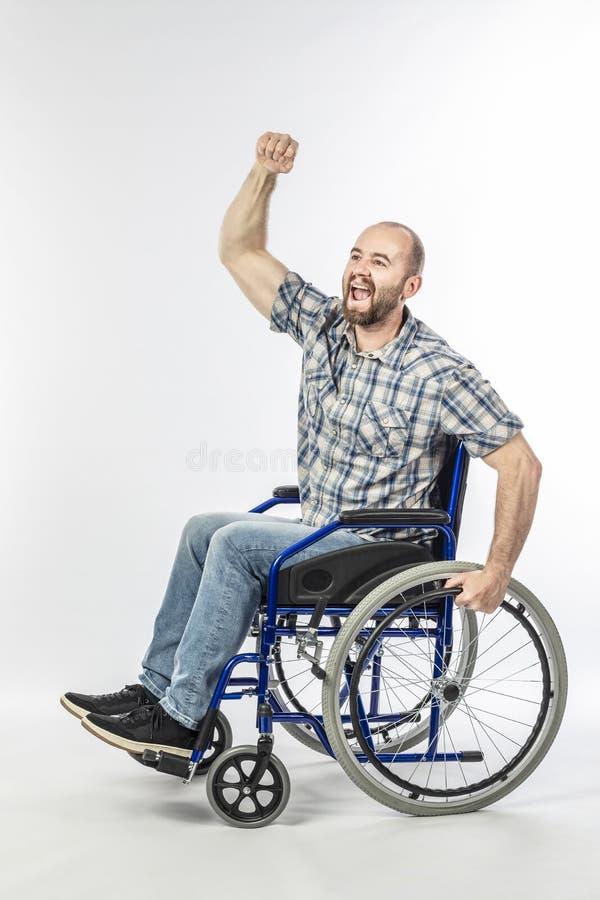 O homem deficiente na cadeira de rodas com bra?o aumentou imagem de stock