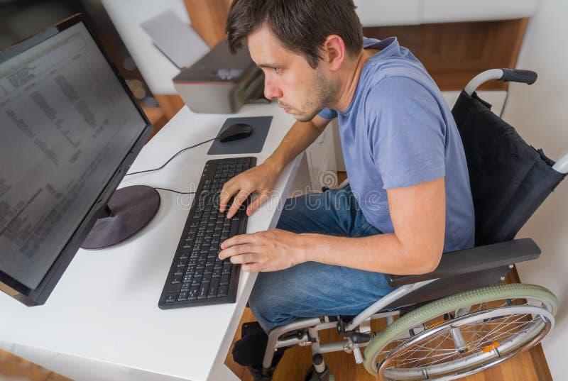 O homem deficiente deficiente na cadeira de rodas está trabalhando com o computador no escritório fotos de stock