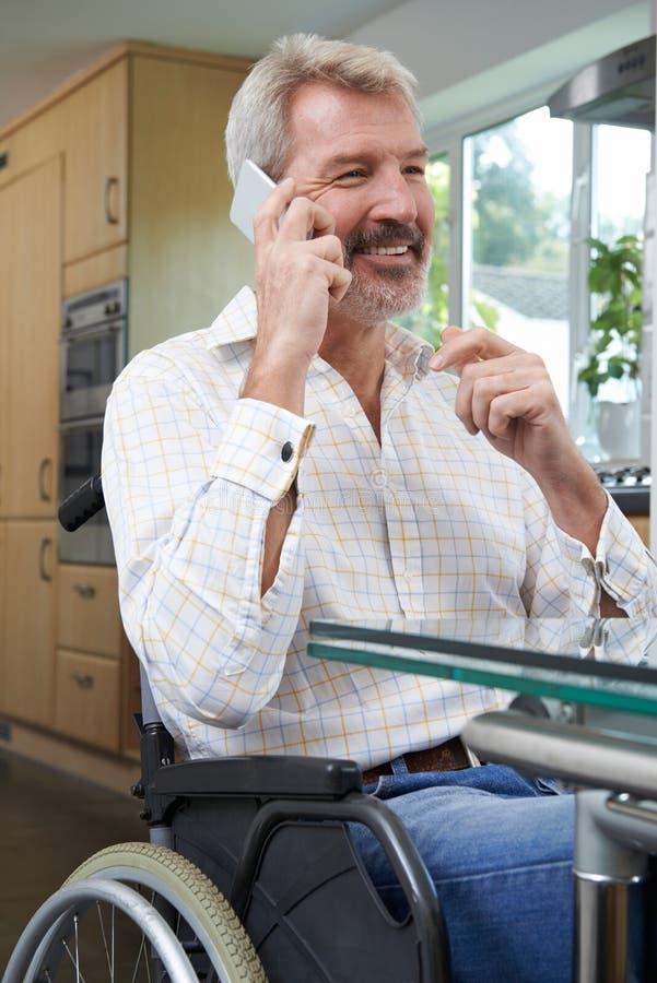 O homem deficiente na fatura da cadeira de rodas chama o telefone celular em casa imagens de stock royalty free