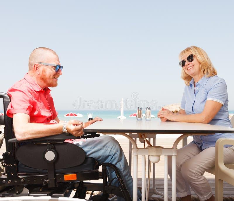 O homem deficiente senta-se com uma mulher imagens de stock