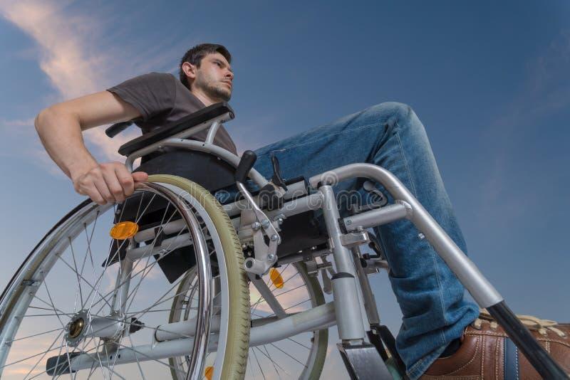 O homem deficiente tido desvantagens está sentando-se na cadeira de rodas C?u no fundo fotos de stock royalty free