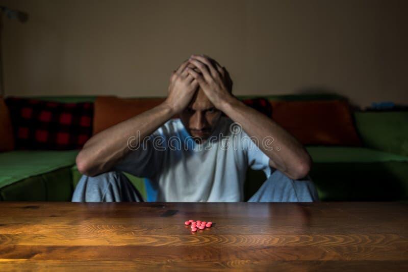 O homem deprimido que sofre da depress?o suicida quer cometer o suic?dio tomando drogas e comprimidos fortes do medicamento imagens de stock