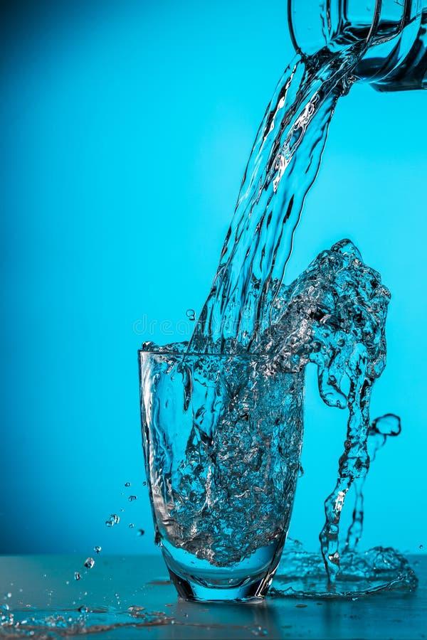 O homem derrama a água do vidro imagens de stock
