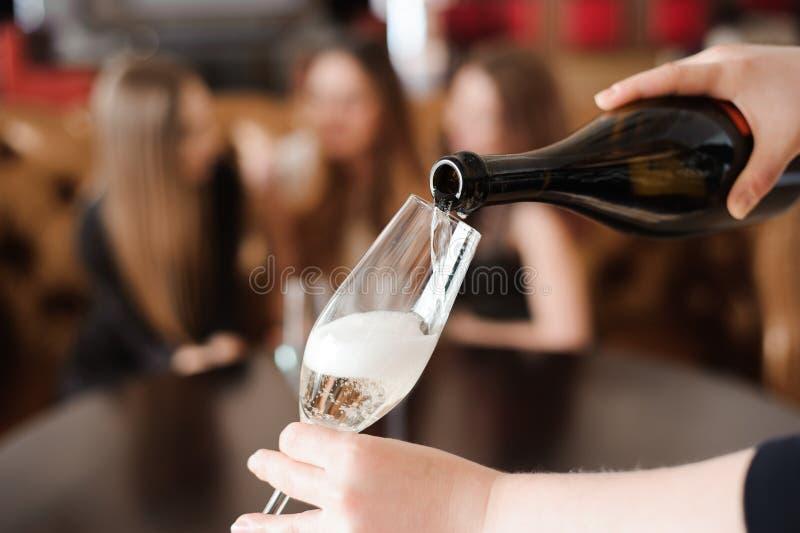 O homem derrama o champanhe em uns copos de vinho em um café imagem de stock royalty free