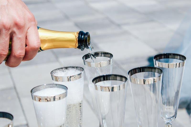 O homem derrama o champanhe em vidros Close-up fotografia de stock royalty free