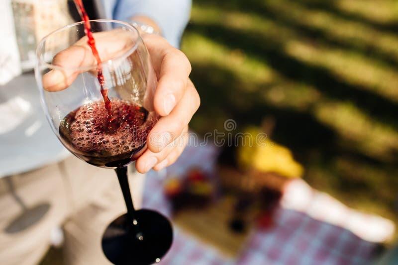 O homem derrama o vinho tinto no vidro no piquenique imagens de stock