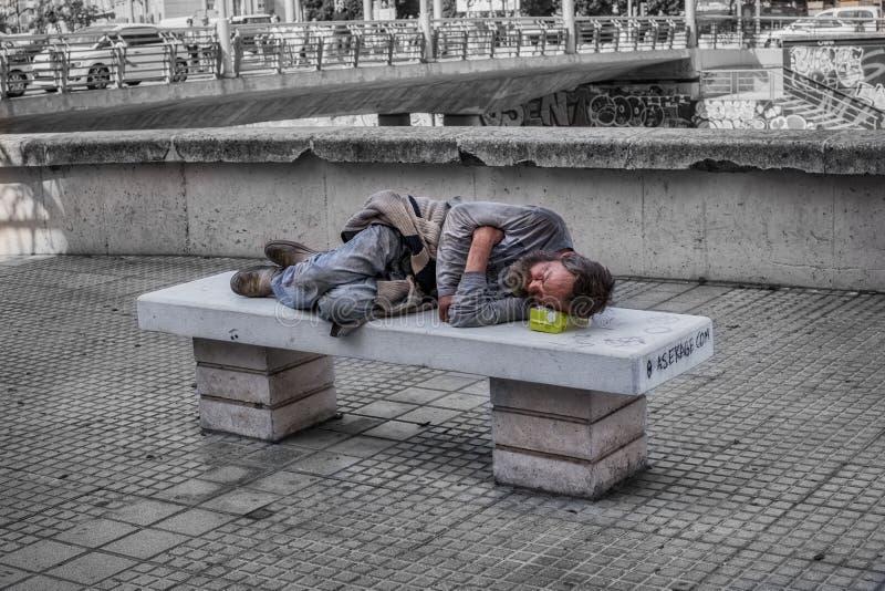 O homem desabrigado dorme no banco de pedra na baixa fotografia de stock