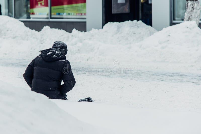 O homem desabrigado implora por joelhos da esmola na neve foto de stock