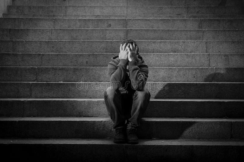 O homem desabrigado novo perdeu na depressão que senta-se nas escadas à terra do concreto da rua foto de stock