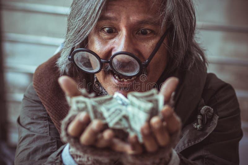 o homem desabrigado obteve a muito dinheiro nele as mãos que fazem a cara feliz com sorriso fotografia de stock royalty free