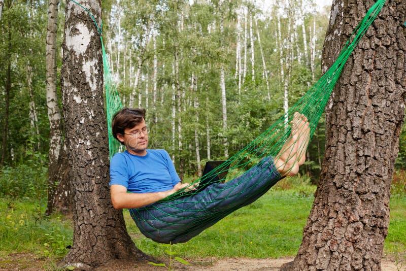 O homem descalço dos jovens nos vidros com reclina na rede fotos de stock royalty free