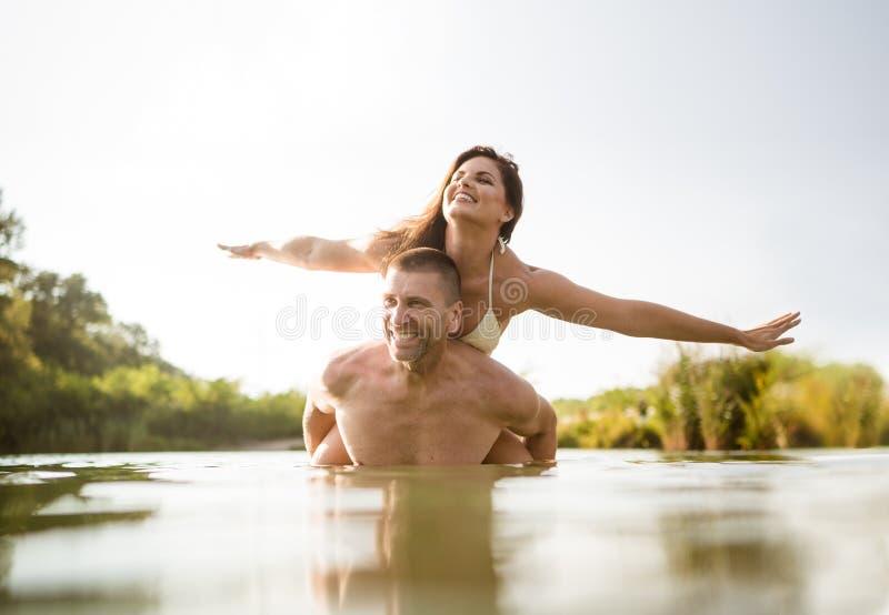O homem descamisado dá a sua esposa um passeio do reboque no lago fotografia de stock