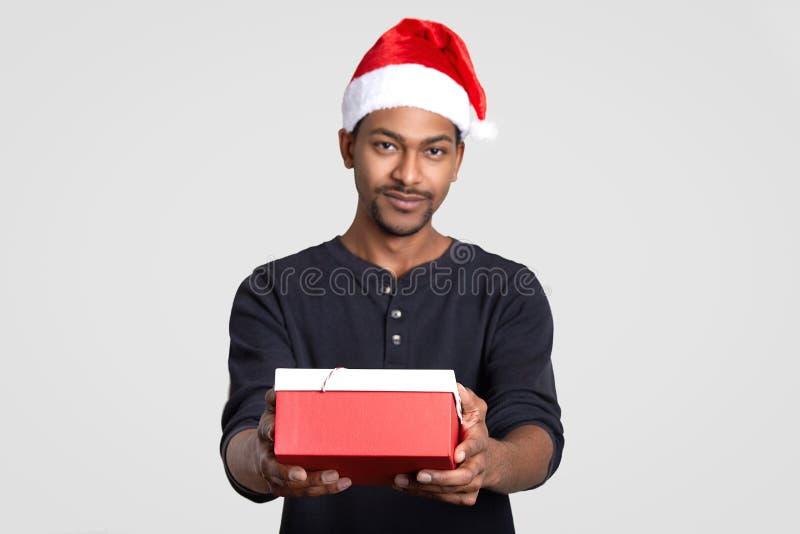 O homem descascado escuro de Santa Claus guarda a caixa de presente, felicita-o com ano novo, modelos contra o fundo branco Foco  foto de stock royalty free
